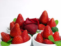 Strawberry. Some strawberry little bowls with mint on white background and one valentine rose stock image
