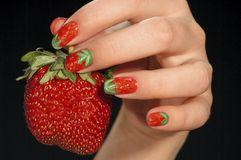 Strawberry. In a female hand, manicure, red Royalty Free Stock Photo