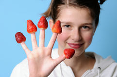 Strawberry. Teenager with five strawberries fingers royalty free stock images