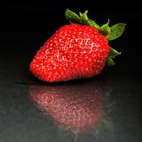 Strawberry against black background. Perfect ripen strawberry against black background Royalty Free Stock Photo