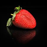 Strawberry against black background. Perfect ripen strawberry against black background Royalty Free Stock Photography