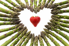 Strawberry Amidst A Heart Made Of Asparagus Spears Royalty Free Stock Photos