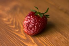 Strawberry on the background of a beautiful lacquered wood close-up royalty free stock photo