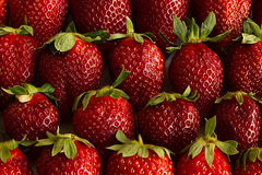 Strawberry background of whole strawberries.  Colorful ripe strawberries. Fruit background. Strawberry pattern. Spring, summer bac Stock Photos
