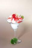 Strawberry and banana dessert. Martini glass full of pieces of fresh banana, strawberries and cream with organic yogurt decorated with strawberries flower stock photos