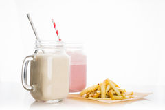 Strawberry and banana milkshakes. On the white background royalty free stock photos