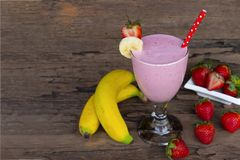 Strawberry and banana smoothie colorful fruit juice milkshake blend beverage healthy on a wooden background. royalty free stock images