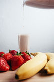 Strawberry banana smoothie fresh blended on wood table Royalty Free Stock Photos