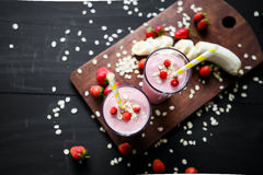 Strawberry and banana smoothie in the glass on black background. Smoothie with in cups on a black background Royalty Free Stock Photos