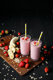 Strawberry and banana smoothie in the glass on black background. Smoothie with in cups on a black background Stock Image