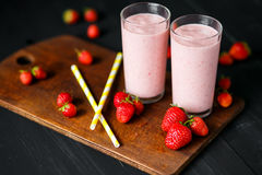 Strawberry and banana smoothie in the glass on black background. Smoothie with in cups on a black background Royalty Free Stock Image