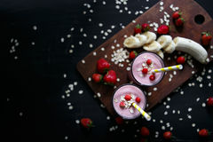 Strawberry and banana smoothie in the glass on black background. Smoothie with in cups on a black background Stock Photos