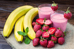 Strawberry and banana smoothie in the glass. Fresh strawberries. And bananas on the old wooden background. Fresh strawberry banana smoothie with mint on a Royalty Free Stock Photography