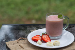 Strawberry and banana smoothie. Strawberry banana smoothie with strawberry and banana slices on the white plate in nature Royalty Free Stock Photography