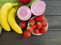 Strawberry banana smoothies on a black wooden background. Healthy food Royalty Free Stock Photography