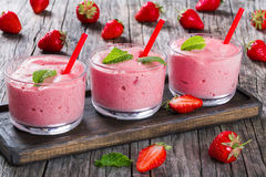 Strawberry Banana Smoothies Cups with straws and mint leaves Stock Images