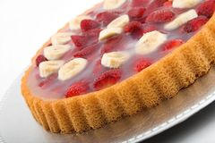 Strawberry banana torte. Fruit torte glazed on platter stock image