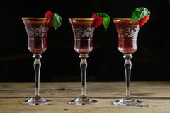 Three strawberry and basil cocktails in vintage glasses stock photo