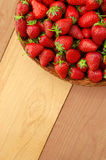 Strawberry in basket on colorful wooden table Royalty Free Stock Image