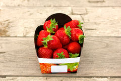 Strawberry Basket on wooden table. A basket of mouthwatering freshly picked strawberries on a natural wooden table stock photos
