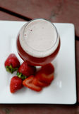 Strawberry beer with plated strawberries. Strawberry beer with strawberries on white plate on deck Royalty Free Stock Photography