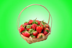 Strawberry berries in the basket. On a green background Stock Photos