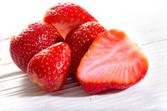 Strawberry berries, whole and cut, on white boards Royalty Free Stock Image