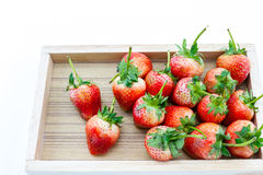 Strawberry berries in a wooden tray on a white background. Strawberry ripe berries in a wooden tray on a white background Stock Image
