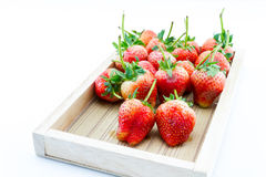 Strawberry berries in a wooden tray on a white background. Strawberry ripe berries in a wooden tray on a white background Stock Images