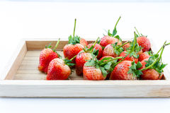 Strawberry berries in a wooden tray on a white background. Strawberry ripe berries in a wooden tray on a white background Royalty Free Stock Image