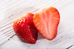 The strawberry berry cut in half on a white board Stock Photo