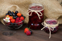 strawberry, black currant and raspberry jam on a rustic table. Stock Photos
