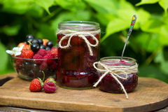 Strawberry, black currant and raspberry jam on a rustic table. Royalty Free Stock Photos