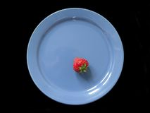 Strawberry on blue plate. Isolated black background royalty free stock photos