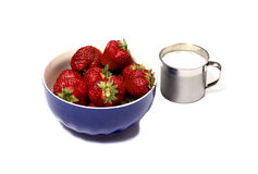 Strawberry in a blue soup plate and a milk mug Royalty Free Stock Photography