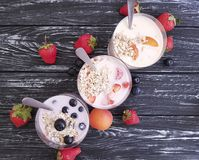 Strawberry, blueberry apricot homemade organic fresh yogurt delicious oatmeal muesli on a black wooden background stock photos