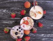 Strawberry, blueberry apricot organic fresh yogurt delicious oatmeal muesli on a black wooden background. Strawberry, blueberry apricot yogurt oatmeal muesli on Royalty Free Stock Image