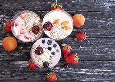 Strawberry, blueberry apricot fresh yogurt delicious oatmeal muesli on a black wooden background. Strawberry, blueberry apricot yogurt oatmeal muesli on a black Stock Image