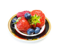 Strawberry and blueberry dessert. Fruits delight dessert - strawberries, blueberries and raspberry on elegant black and golden antique dish. Isolated on white Stock Image