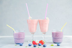 Strawberry and Blueberry Fresh and Cold Smoothies. Pink and purple Smoothie in Glasses and some Fresh Berries around. Strawberry, blueberries, banana, milk and stock photo