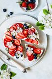 Summer Berry No Bake Cheesecake. Strawberry and Blueberry No Bake Cheesecake Decorated with Spring Flowers, copy space for your text stock photo