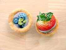 Strawberry and blueberry tart, top view on wooden table Royalty Free Stock Images