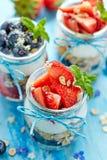 Strawberry blueberry yogurt parfait with addition of muesli, coconut flakes and fresh mint Stock Images