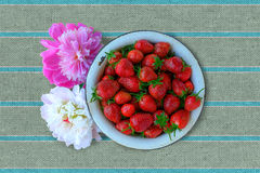 Strawberry in a boil. Garden strawberry in a old boil with peonies royalty free stock photography