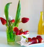 Strawberry bouquet in Green Glass With orchid on White Plate With Orchids royalty free stock image