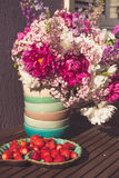 Strawberry and bouquet of  pink white and violet flowers Stock Photos
