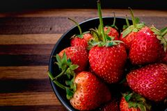 Strawberry in bowl black Royalty Free Stock Photography