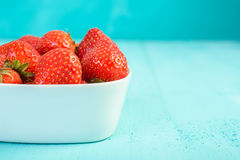 Strawberry Bowl On Blue Wood Stock Photos