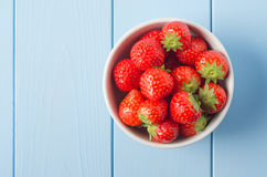 Strawberry Bowl Overhead. Overhead shot of a white china bowl containing red strawberries with leaves intact, positioned on the right side of a light blue wood Royalty Free Stock Photos