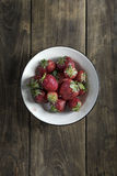 Strawberry in a bowl on wooden table Royalty Free Stock Photography